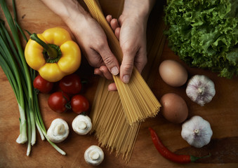 Top view of woman hands holding raw spaghetti on wooden table with eggs, vegetables and greenery. Female cook preparing mediterranean meal.