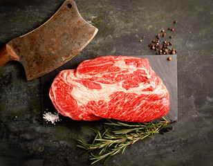 veal steak marbled basalt, a knife for meat, rosemary on a dark background
