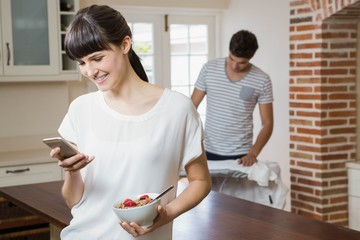 Woman using mobile phone while having breakfast cereals