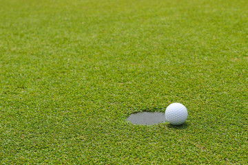 Golf ball at the edge of putting cup hold at outdoor putting green