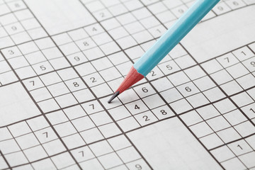 Crossword sudoku and blue pencil for entertainment, popular conundrum