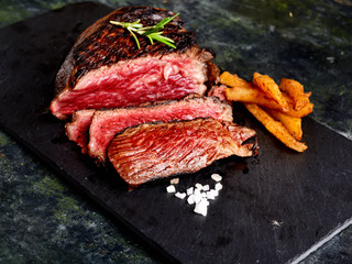 fried steak, potatoes on a dark background