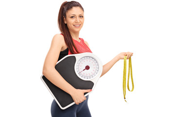 Girl holding weight scale and measuring tape