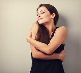 Happy strong sporty woman hugging herself with natural emotional
