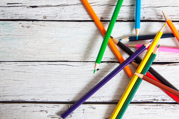Stack of colored pencils in a glass on wooden background
