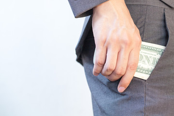 Business man's hand hiding money in pocket - Corruption and Fraud Concept