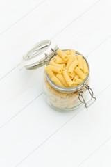 Raw tortiglioni pasta on a glass jar