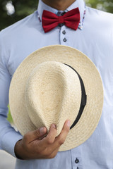 Man in shirt, red bow-tie holding white wicker hat