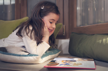 Girl reading a book on the sofa - 5