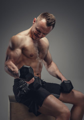 A man holds a pair of dumbbells.