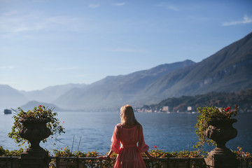 girl in a beautiful dress standing on the viewpoint with views of Lake Como