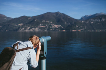man looking in the telescope on the shore of Lake Como