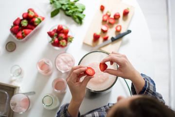 Man preparing a strawberry milkshake