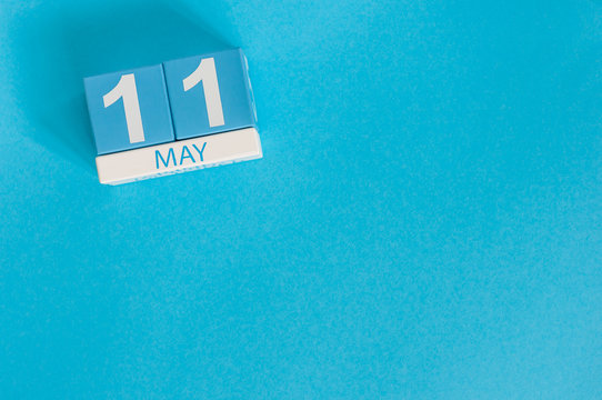 May 11th. Image of may 11 wooden color calendar on blue background.  Spring day, empty space for text