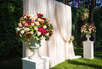 wedding arch with flowers on the green leaves background
