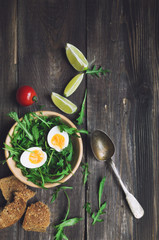 Wall Mural - Breakfast salad with egg and arugula in wooden bowl