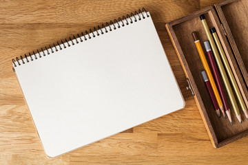 Blank notebook with pencils on the desk. Overhead