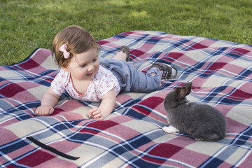 Beautiful baby girl playing outdoor with bunny on blanket.