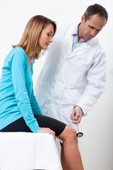 médecin qui teste les réflexes d'une patiente