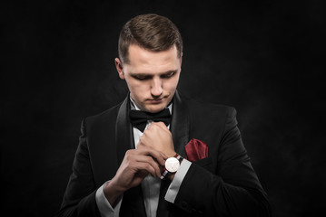 Elegant young fashion man looking at his watch .