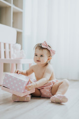 Cute baby girl playing in a white room in the morning with toys