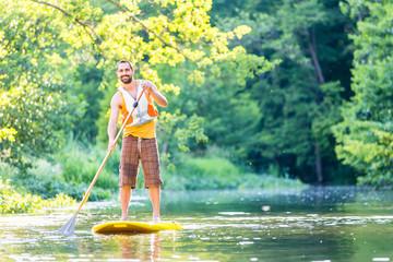 Mann beim Stehpaddeln auf SUP auf Fluss