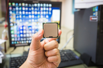 CPU in hand with desktop PC computer at office background. soft focus