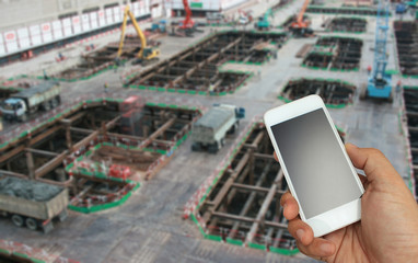 hand holding the smartphone on blurred construction site backgro