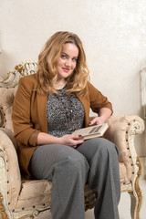 Woman blonde in a suede jacket and pants around the fireplace