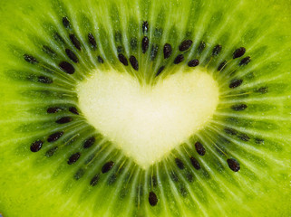 Green fruit kiwi close up with heart, green background
