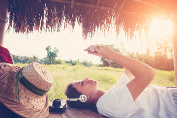 Young happy girl resting outdoors with mobile phone in hands and listening music (intentional sun glare and vintage color)