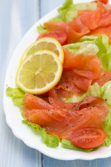 salad with smoked salmon on white dish on blue wooden background