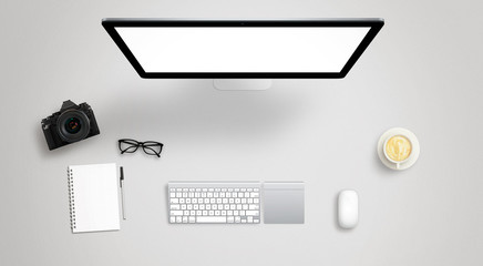 Isolated computer display for mockup on work desk with keyboard, mouse, coffee, camera, notebook, glasses, pencil.