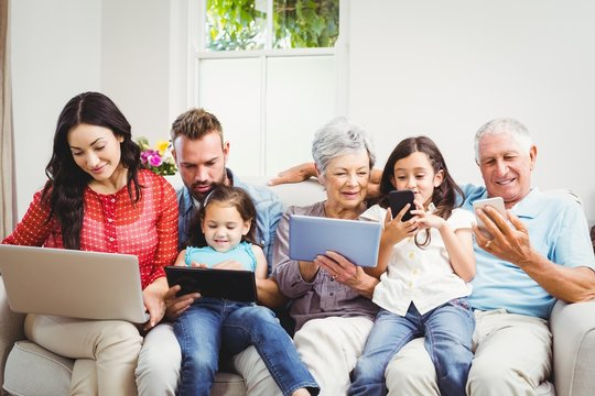 Family using technologies while sitting in sofa