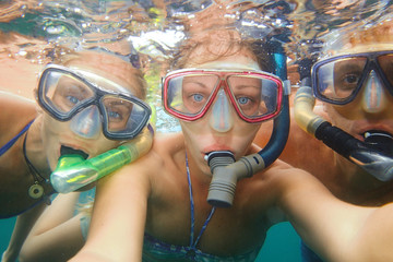 Underwater photo of a young people snorkeling at tropical ocean