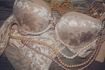 Sexy lace lingerie and pearls on a wooden board