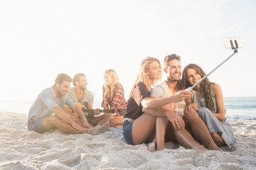 Smiling friends sitting on sand singing and taking selfies