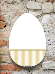 Close-up of one hanged decorated Easter egg blank frame with clip against weathered brick wall background