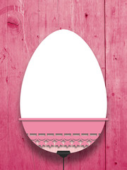 Close-up of one hanged decorated blank Easter egg frame with pink decoration against red wooden boards background