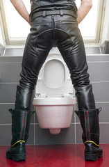 man in leather gear standing at toilet