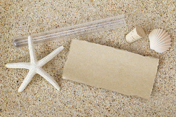Blank brown paper outside a tube with cork lid removed on a sandy beach with white starfish and seashell. Message in a bottle style