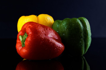 colorful peppers over dark background