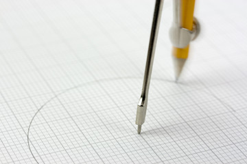 Close up of a compass on graph paper