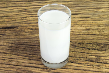 Milk in a glass on wooden background