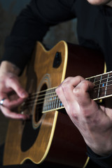Young man playing on acoustic guitar. Selective focus