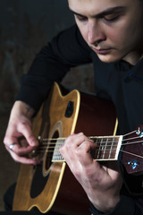 Young man playing on acoustic guitar. Selective focus.
