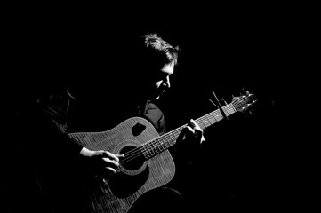 Male musician playing on acoustic guitar. Black and white photo.