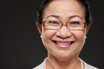 Face of Asian senior woman in glasses smiling at camera