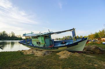 Old abandoned fisherman boat on the riverside