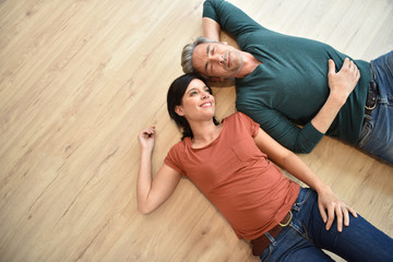 Upper view of couple laying on wooden floor